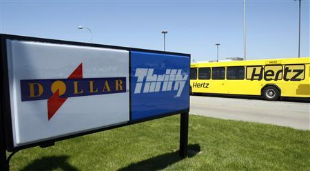 A Hertz rent-a-car shuttle bus drives by a Dollar Thrifty rent-a-car lot near the Detroit Metropolitan airport in Romulus, Michigan in this May 9, 2011, file photo. REUTERS/Rebecca Cook/Files