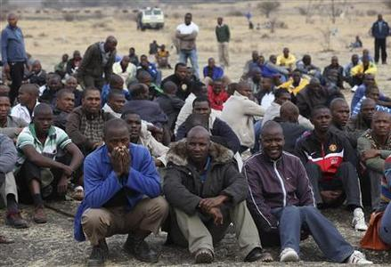 Mine workers gather while on strike near the scene of a shooting at Marikana, in the north western province August 27, 2012. REUTERS/Mike Hutchings