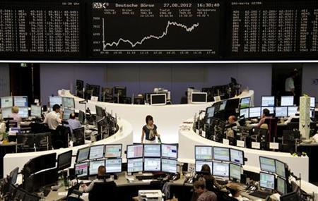 Traders are pictured at their desks in front of the DAX board at the Frankfurt stock exchange August 27, 2012. REUTERS/Remote/Marte Kiessling