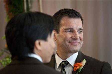 Shawn Klein smiles during his marriage ceremony to Phil Fung, his life-partner of 18 years, on the 61st floor of the Empire State Building in New York February 14, 2012. REUTERS/Andrew Burton