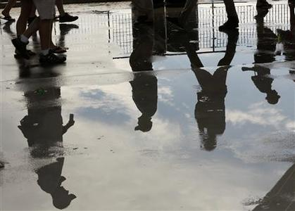 Spectators walking past are reflected on a puddle of water during a rain delay at the U.S. Open tennis tournament in New York August 27, 2012. REUTERS/Kevin Lamarque