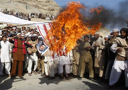 Afghan protesters burn a U.S. flag during a protest in Jalalabad province in this February 24, 2012 file photo. Protests have raged across Afghanistan over the desecration of copies of the Muslim holy book at a NATO military base with riot police and soldiers on high alert braced for more violence. REUTERS/Parwiz/Files