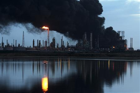 A column of smoke rises as fuel storage tanks are seen on fire at Amuay oil refinery in Punto Fijo in the Peninsula of Paraguana, August 27, 2012. REUTERS/Marife Cuauro