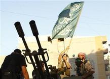 Члены Свободной армии Сирии размахивают исламским флагом в районе Дамаска Гута 27 августа 2012 года. Сирийские повстанцы сбили правительственный вертолет, обстреливавший район Джобар в окрестностях Дамаска, во время кровопролитных столкновений между мятежниками и лояльными режиму Башара Асада военными в понедельник, сообщили очевидцы. REUTERS/Omar Khani