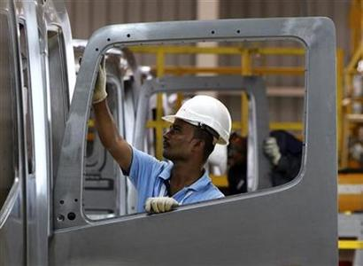 An employee installs a window on a BharatBenz truck inside Daimler's new factory in Oragadam, in Tamil Nadu April 18, 2012. REUTERS/Babu/Files