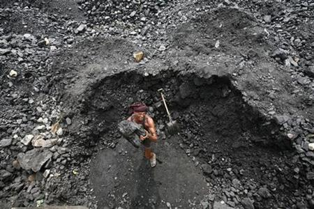 A labourer loads coal onto a truck at a coal yard on the outskirts of Jammu August 24, 2012. REUTERS/Mukesh Gupta