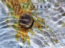 """Монета в один евро лежит на карте Греции в Мюнхене, 21 августа 2012 г. Греция планирует создать """"специальные экономические зоны"""", чтобы привлечь частные инвестиции и вытащить погрязшую в долгах экономику из рецессии, сообщило во вторник греческое правительство. REUTERS/Michaela Rehle"""