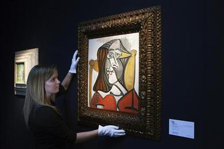 An employee holds Pablo Picasso's ''Femme au fauteuil'' at Christie's auction house in London February 2, 2012. REUTERS/Finbarr O'Reilly