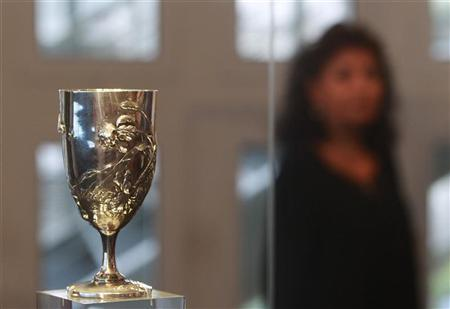 A visitor stands behind the Breal's Silver Cup, which was awarded to Spyros Louis, winner of the marathon race at the 1896 Olympics in Athens, during a presentation ceremony at the Athens Acropolis Museum August 27, 2012. REUTERS/John Kolesidis