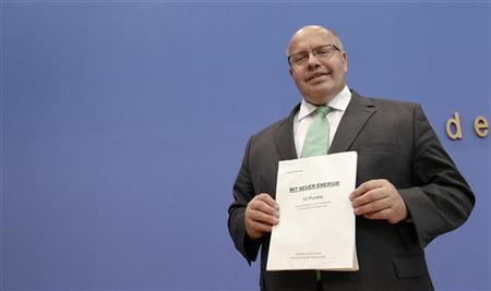 Germany's Environment Minister Peter Altmaier holds up his script titled ''With new energy - 10 topics'' before a news conference in Berlin August 16, 2012. REUTERS/Tobias Schwarz