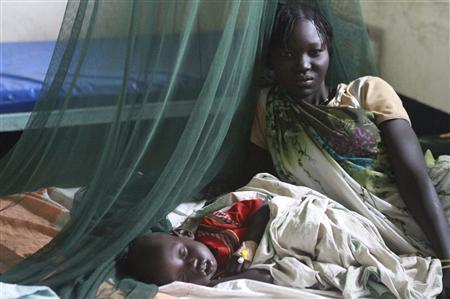 A woman rests with her 18-month-old daughter, who is being treated for malaria by International Medical Corps doctors, at Akobo County Hospital in South Sudan, in this July 25, 2012 file picture. REUTERS/Margaret Aguirre/International Medical Corps/Handout/Files
