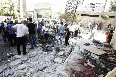 Wreckage of vehicles and blood are seen after a car bomb exploded at the entrance to a Druze cemetery in the Jaramana district of southeast Damascus August 28,2012. REUTERS-Khaled al-Hariri