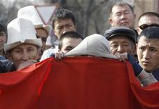 Человек утирает лицо национальным флагом Киргизии в толпе соотечественников в Бишкеке 9 апреля 2010 года. Рассерженная толпа во вторник разогнала участников аукциона по продаже лицензий на месторождения золота и угля, проходившего в прямом телеэфире, сорвав попытку правительства испытывающей нужду в средствах Киргизии привлечь инвестиции. REUTERS/Denis Sinyakov