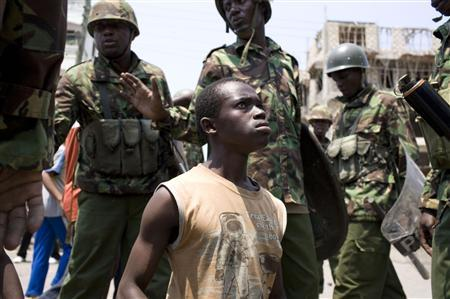 A man accused of allegedly instigating street riots is detained by Kenyan policemen in the coastal city of Mombasa, August 28, 2012. REUTERS/Siegfried Modola