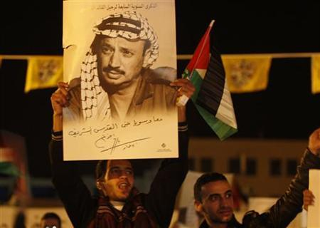 A Palestinian holds up a poster depicting late Palestinian leader Yasser Arafat during a ceremony marking the seventh anniversary of his death, in the West Bank city of Hebron November 13, 2011. REUTERS/ Mussa Qawasma/Files