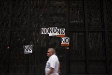 "A man walks past posters that read, ""No to cuts,"" after a civil servants' protest against government austerity measures in front of the Treasury and Public Administration Ministry in Madrid August 10, 2012. REUTERS/Susana Vera"