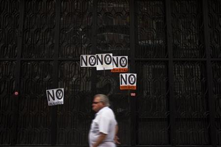 A man walks past posters that read, ''No to cuts,'' after a civil servants' protest against government austerity measures in front of the Treasury and Public Administration Ministry in Madrid August 10, 2012. REUTERS/Susana Vera