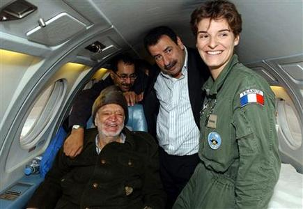 Palestinian leader Yasser Arafat (L) sits in a plane as he heads to France for medical treatment in this October 29, 2004 file photo. REUTERS/Hussein Hussein/Handout/Files