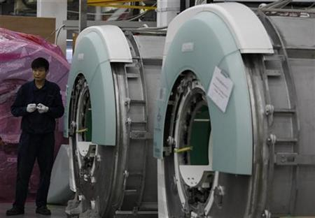 A worker stands beside two magnetic resonance imaging (MRI) machines being assembled at Siemens MR Center located at the Shenzhen High-Tech Industrial Park in the southern Chinese city of Shenzhen in Guangdong province November 25, 2008. REUTERS/Bobby Yip