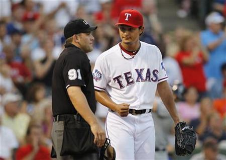 Texas Rangers starting pitcher Yu Darvish talks with home plate umpire Brian Knight in the second inning of the team's MLB American League baseball game against the Tampa Bay Rays in Arlington, Texas, August 28, 2012. REUTERS/Mike Stone