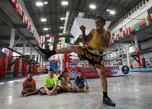 A trainer at the Muay Thai Institute shows some steps to children during training in Bangkok August 26, 2012. Once the province of men in dark, smoky stadiums and shadowed by an image of violence, Thailand's ancient martial art of Muay Thai is being reborn - as a fitness regime. Picture taken August 26, 2012. REUTERS/Sukree Sukplang