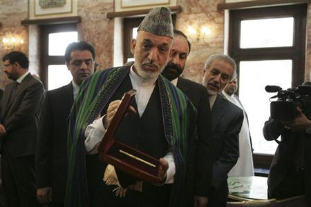 Afghanistan's President Hamid Karzai (C) gestures as he poses with a case containing a pen which belonged to the country's former King Shah Amanullah Khan during a ceremony at the Presidential Palace in Kabul August 27, 2012. REUTERS/Ahmad Massoud/Pool