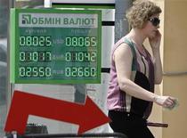 Женщина разговаривает по мобильному, входя в пункт обмена валют в Киеве 23 мая 2012. Украинская гривна в среду достигла 33-месячного минимума к доллару, ослабнув до 8,116, показали данные Рейтер. REUTERS/Gleb Garanich