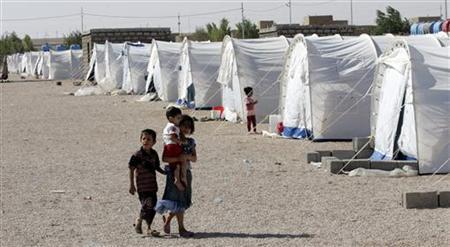 A Syrian girl carries her brother as they walk at a refugee camp in al-Qaim, Anbar province August 15, 2012. REUTERS/Ali al-Mashhadani
