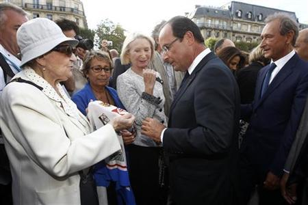 French President Francois Hollande (C) and Paris mayor Bertrand Delanoe (R) listen to an elderly woman as they attend a ceremony marking the 66th anniversary of the Liberation of Paris, Agust 25, 2012. REUTERS/Jacky Naegelen/POOL