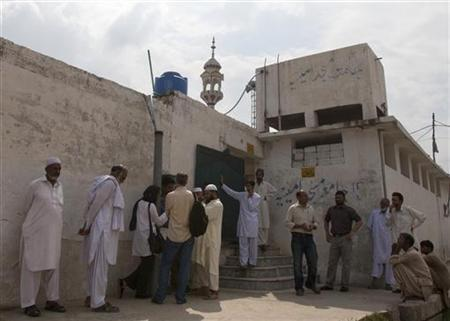 Members of the media and residents gather outside a mosque near the locked family house of Rimsha Masih, a Pakistani Christian girl accused of blasphemy, on the outskirts of Islamabad August 23, 2012. REUTERS/Faisal Mahmood