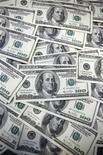 Долларовые купюры в банке в Сеуле 20 сентября 2011 года. Крупнейший в РФ производитель стали - горно-металлургическая группа Евраз - показала чистый убыток $50 миллионов в первом полугодии 2012 года после прибыли $263 миллиона годом ранее, сообщила компания в четверг. REUTERS/Lee Jae-Won