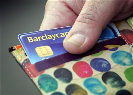 A Barclays Bank's customer takes out a bank card in London February 21, 2006. REUTERS/Stephen Hird