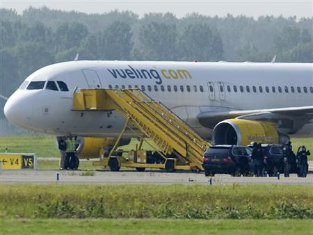 A Vueling plane parks at a field near Amsterdam Airport after a hijack scare August 29, 2012. REUTERS/Robin van Lonkhuijsen/United Photos