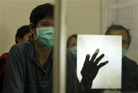 The hand of doctor Marion Aritonang is reflected on a glass pane as she speaks about tuberculosis in front of newly diagnosed tuberculosis patients at the Indonesian Union Against Tuberculosis clinic in Jakarta, April 4, 2011. REUTERS/Beawihart/Files