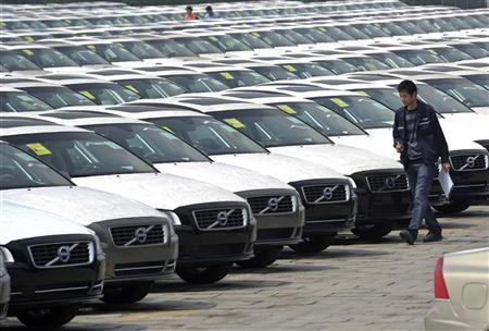 An employee walks past newly assembled Volvo cars lined up at a parking lot of a Ford manufacturing plant in Chongqing municipality, April 20, 2012. REUTERS/Stringer