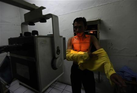 A patient suspected of having tuberculosis puts on his shirt after an x-ray at the Indonesian Union Against Tuberculosis clinic in Jakarta, April 4, 2011. REUTERS/Beawiharta