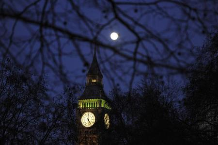 The full moon is pictured through trees as it shines over the Big Ben clock tower in London January 18, 2011. REUTERS/Paul Hackett