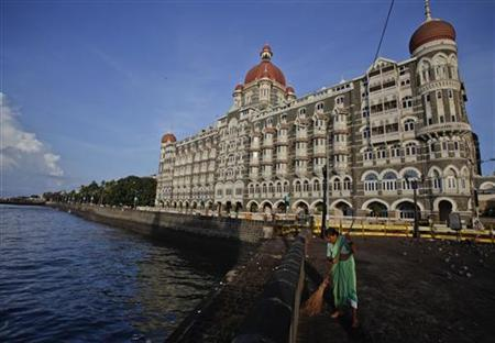 A municipal worker sweeps a pavement in front of the Taj Mahal hotel, one of the sites of the 2008 militant attacks, in Mumbai May 31, 2011. REUTERS/Vivek Prakash/Files