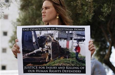 A demonstrator holds a poster depicting activist Rachel Corrie outside the Haifa district court, after the ruling in a civil case August 28, 2012. REUTERS/Amir Cohen