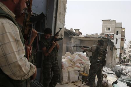 A Free Syrian Army fighter fires an AK-47 rifle at Syrian Army soldiers during clashes in the El Amreeyeh neighborhood of Syria's northwest city of Aleppo August 30, 2012. REUTERS/Youssef Boudlal
