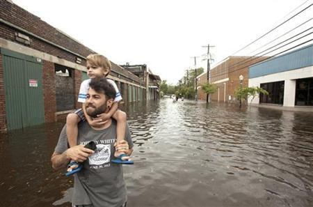Joel Geiger holds his son Jarren Geiger, 4, while surveying the damage in the Olde Towne area after Hurricane Isaac passed through Slidell, Louisiana, August 30, 2012. REUTERS/Michael Spooneybarger