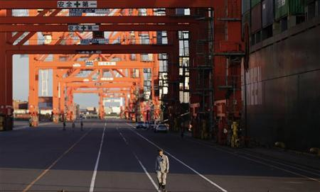 A man walks by containers in Tokyo August 28, 2012.REUTERS/Toru Hanai