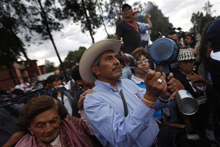 A protester hits a pot during a demonstration outside Mexico's electoral court in Mexico City, August 30, 2012. REUTERS/Edgard Garrido