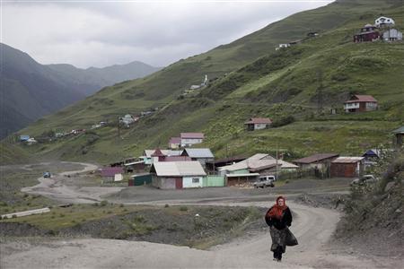 A woman walks along a road in the settlement of Akhty in southern Dagestan, July 4, 2012. REUTERS-Maria Turchenkova