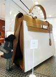 Покупатель рассматривает гигансткую копию сумки Hermes Kelly в бутике Hermes в Наньцзине 17 февраля 2012 года. Французский производитель товаров роскоши Hermes повысил годовой прогноз продаж на фоне высокого спроса в Азии в первом полугодии. REUTERS/China Daily