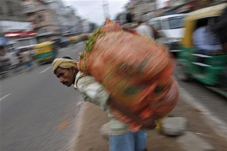 A labourer carrying a sack of vegetables waits to cross a road in the old quarters of Delhi August 31, 2012. REUTERS/Mansi Thapliyal