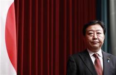 Премьер-министр Японии Йосихико Нода стоит рядом с национальным флагом на пресс-конференции в Токио, 24 августа 2012 г. Правительство Японии в пятницу представило план приостановки некоторых государственных расходов, поскольку у страны уже к октябрю могут кончиться деньги. REUTERS/Yuriko Nakao