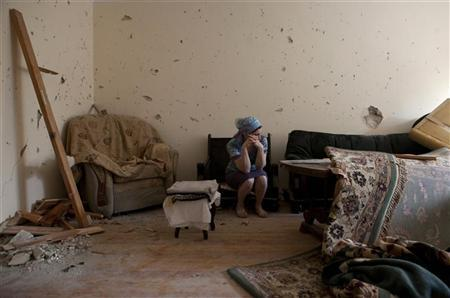 A local resident shows her house, which was seriously damaged during a special antiterrorist operation conducted by the Russian military forces in a building nearby, in the town of Kaspiysk, July 10, 2012. REUTERS/Maria Turchenkova