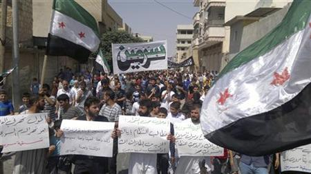 Demonstrators hold Syrian opposition flags and placards during a protest against Syria's President Bashar al-Assad in Sermeen, near Idlib, August 31, 2012. REUTERS/Shaam News Network/Handout