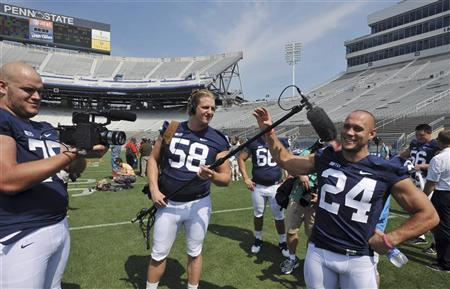 Penn State football players Eric Shrive (75), Adam Gress (58) and Derek Day (24) hold a camera and microphone during Penn State football pre-season media day in State College, Pennsylvania August 9, 2012. REUTERS/Pat Little